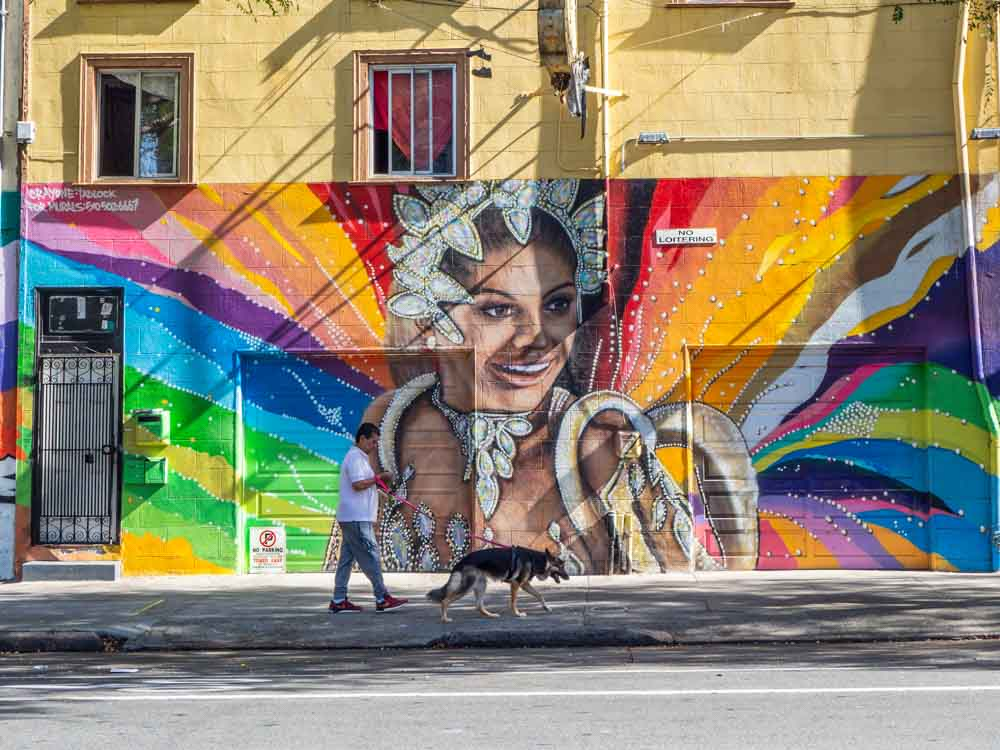 Carnavale mural in the Mission District by Crayone. A woman in costume with a rainbow background.