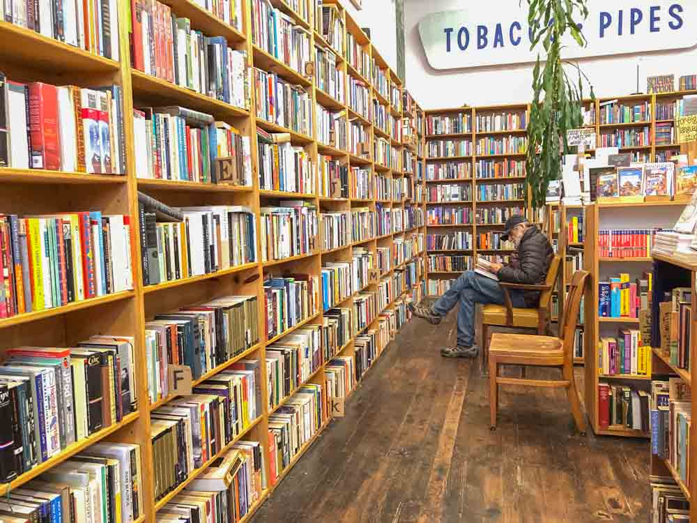 SF independent bookstores: Dog Eared Books. Man in bookshelves