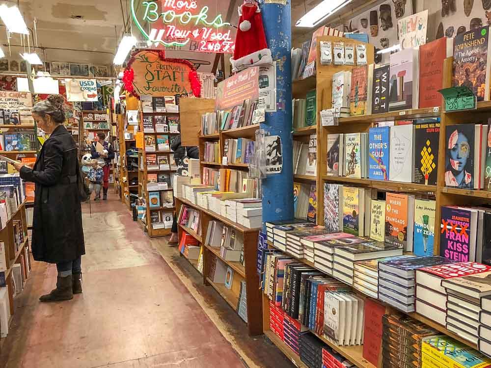 Green Apple Bookstore in San Francisco. Woman in bookshelf