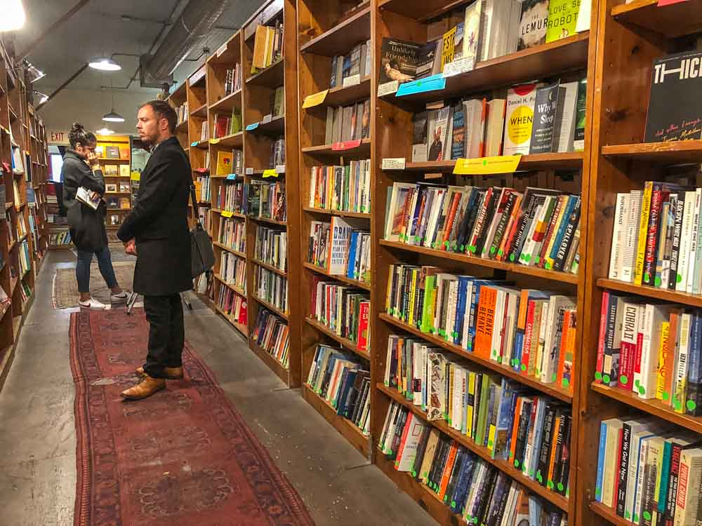 Browser Books in SF. Man browsing bookshelves