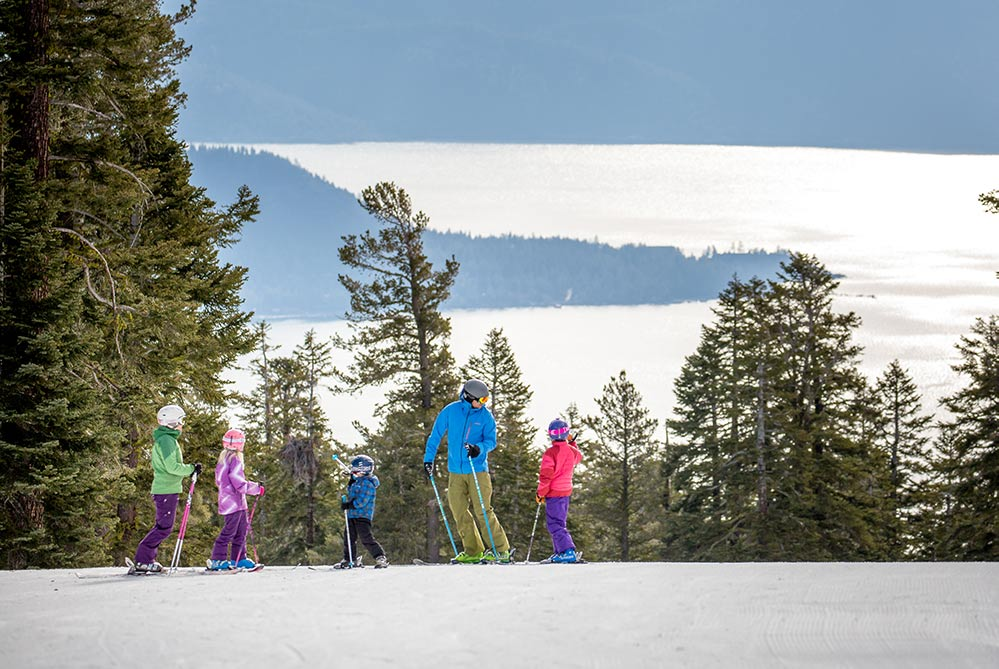 Skiers in Lake Tahoe Northstar ski resort. family on a mountain with pine trees