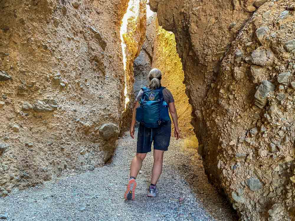 Sidewinder Canyon California - #3 slot canyon. woman with backpack in narrow canyon