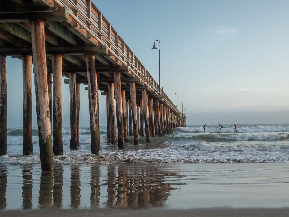 Cayucos beach and pier with surfers at sunset