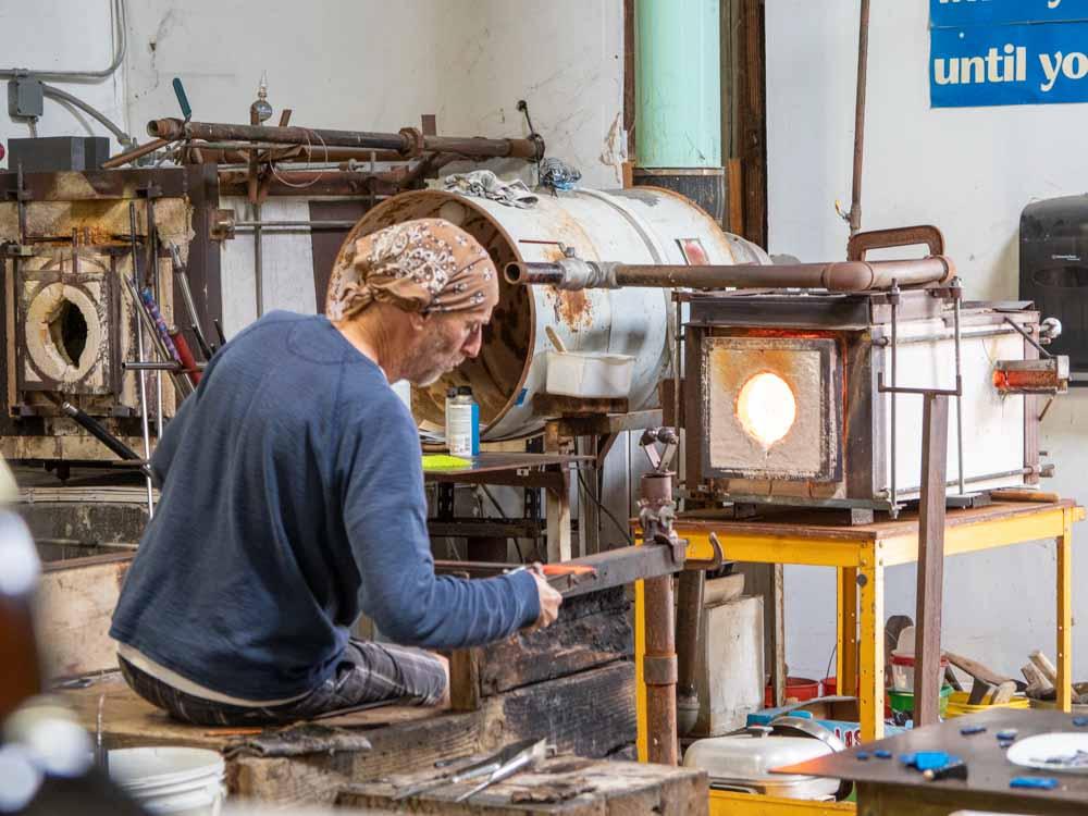 Harmony Glassworks studio. man blowing glass
