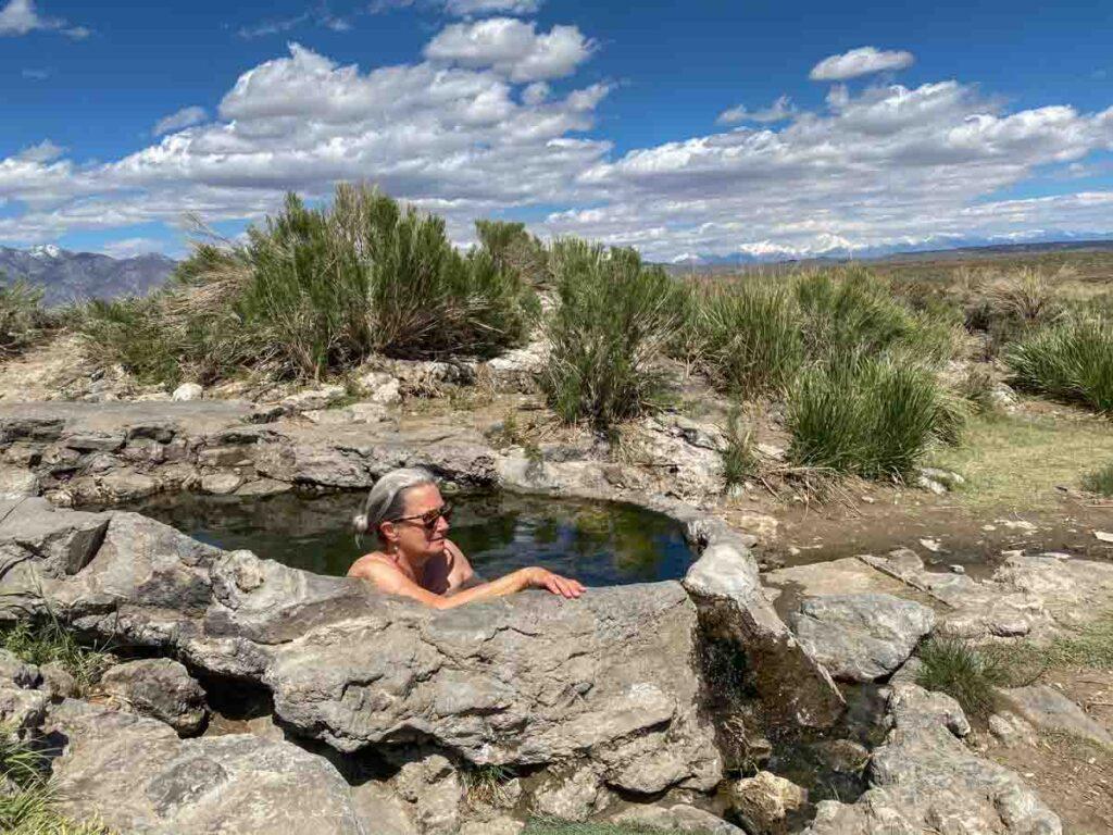 Rock Tub hot springs near Mammoth CA. woman in natural hot tub pool